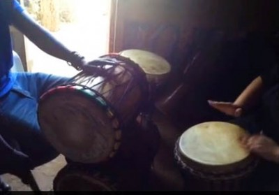 Still photo of me drumming in Senegal (from video).