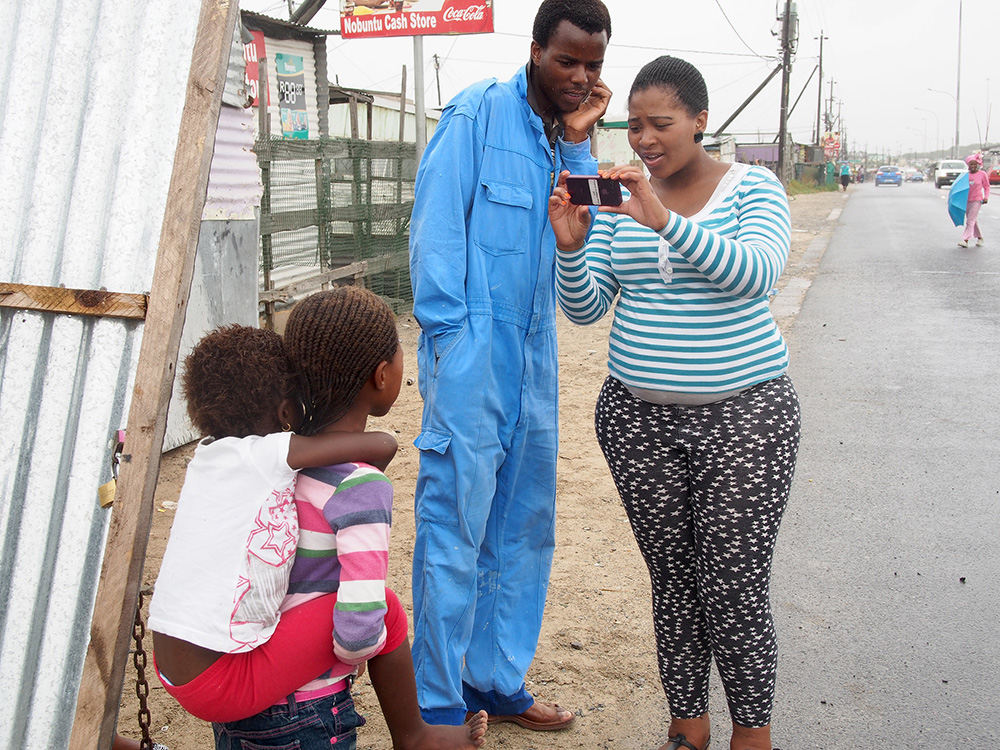 Aviwe, a participant in The Heart of a Woman Project photographs children in Khayelitsha as a curious resident looks on. Shortly after this photo was taken we were warned by shopkeepers and residents to not continue on this road as we neared an informal settlement. They were concerned our iPhones would be stolen. Two men often accompany the women on their photo walk in the Townships.