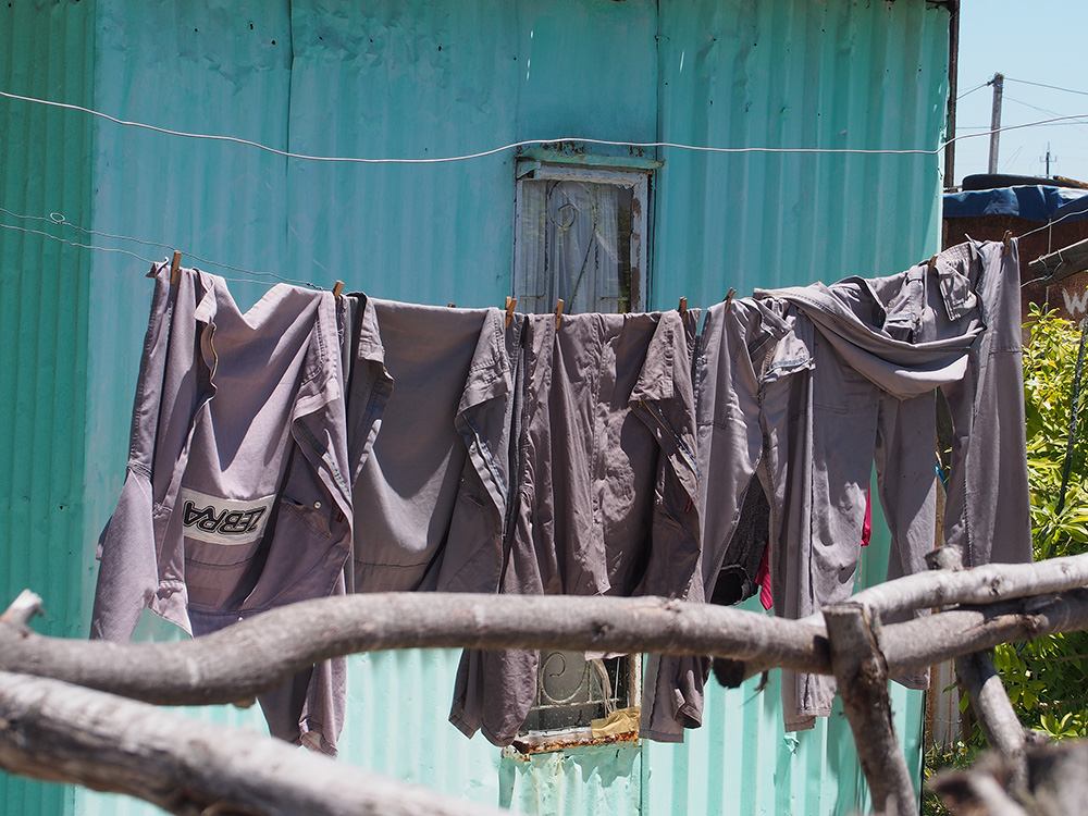 Work clothes hang on a clothesline outside a shack in an informal settlement that we photographed in Khayelitsha. Informal settlements are areas with makeshift dwellings crammed together. Residents do not have access to water in their homes or on their property. They must walk to get water from a communal water source and use communal toilets, which are often in disrepair, and the toilets unclean.