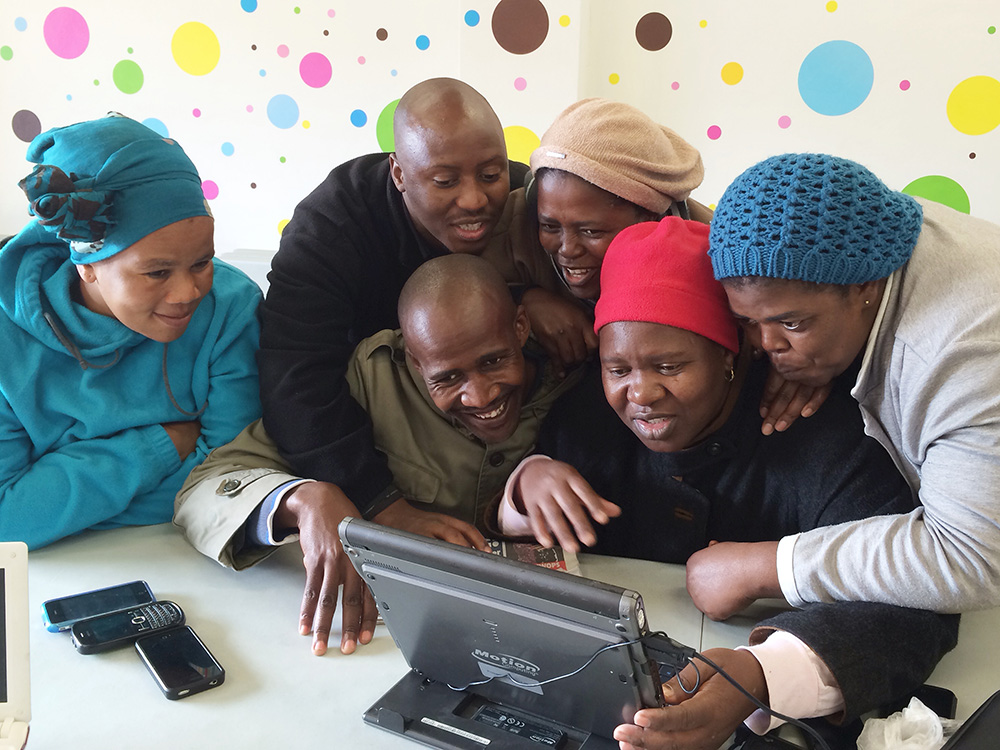 Esther sits at the project's laptop to take her turn learning how to adjust the brightness of the screen. As she placed the pointer on the slider to lower the brightness, she accidentally dragged it too far and the screen went into complete darkness. Development programs give participants the opportunity for peer-to-peer learning, to solve problems and work together. I returned to eKhaya eKasi in May 2014 for 2 weeks to offer further training. Workshops focused on basic computer skills, social media and photo editing.