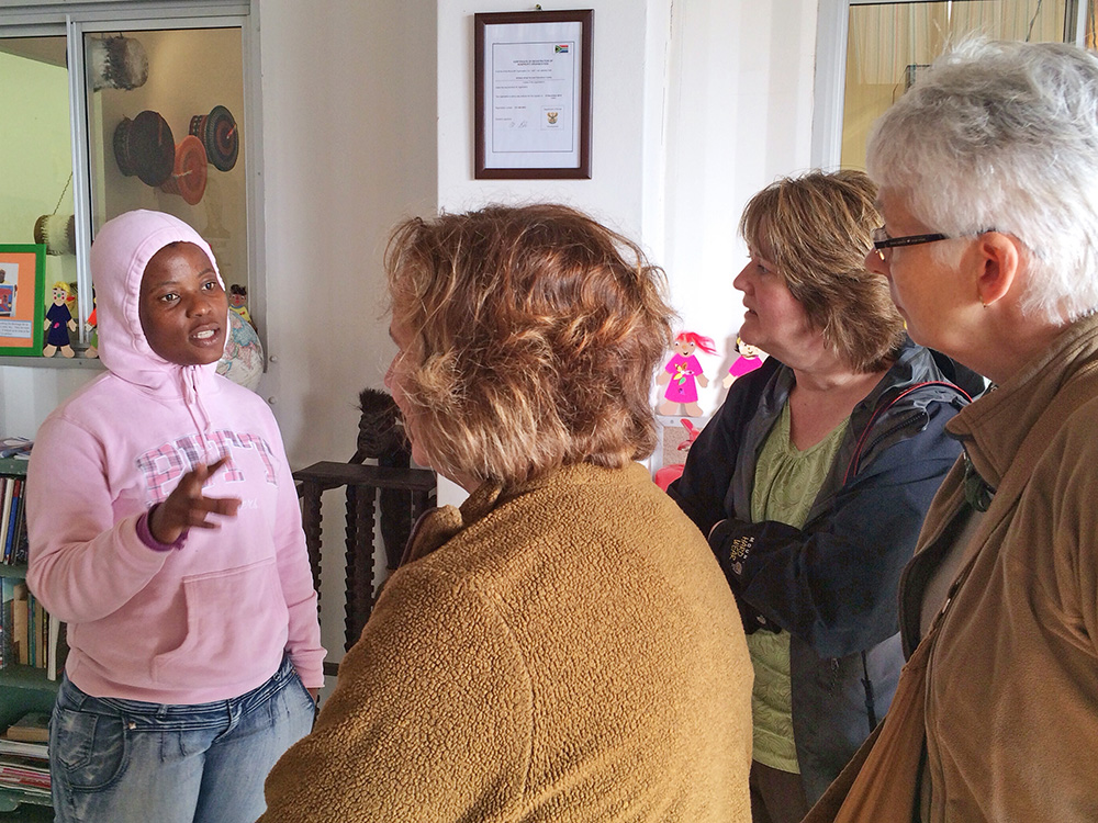 Nwabisa Ndongeni, project leader of The Heart of a Woman Project talks about the program to tourists visiting the centre on tour with Uthando South Africa, a responsible tourism organization.