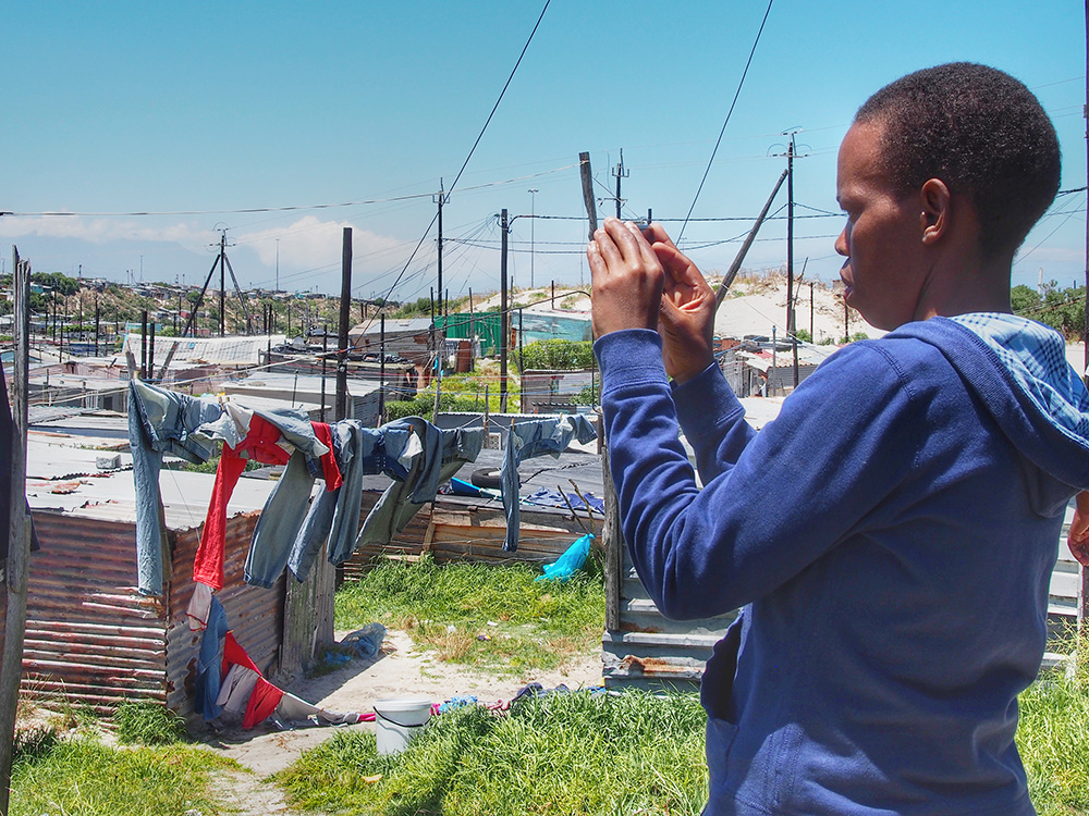 Retsepile Tom, founding member of The Heart of a Woman Project photographs an informal settlement. The population of Khayelitsha is speculated to be over 1 million people. It is difficult to count the numbers as there are several areas where informal settlements are housed. This one has an approximate population of 11,000 people.