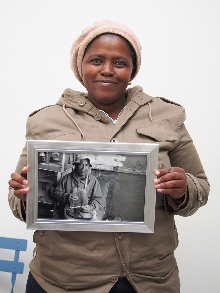 Velisa Wowo, a founding member of The Heart of a Woman Project mobile photography program at eKhaya eKasi proudly displays a framed image of her photo of a shoe repairman in Khayelitsha. This image is Veliswa's series 1.0 postcard and greeting card and was taken with a donated previously owned iPhone 4s. I surprised the women with framed photos of their 'postcard images' in June 2014. They are on display at eKhaya eKasi and were admired by the community and guests at the 1st anniversary photography exhibition and cultural celebration at the centre on November 22, 2014.
