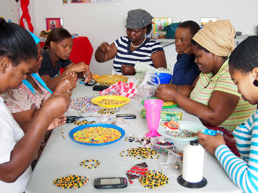 Women make bracelets for a Cape Town company at eKhaya eKasi, a non-profit multi-purpose community centre that offers programs that address unemployment, illiteracy, poverty, health and HIV/AIDS. The skills development programs teach women, mostly mothers and grandmothers, arts, crafts and entrepreneurship. eKhaya eKasi contains an on-site art boutique where participants may sell their work to the tourists that visit. Sales provide revenue to the centre so the programs may continue as well as offers an opportunity for the women to generate an income so they may provide for their families. Women are often the sole providers and caregivers in the Township and face challenges such as high unemployment rates, alcoholism and domestic abuse. The centre also acts as a haven for residents, especially for women and gives them a chance to socialize