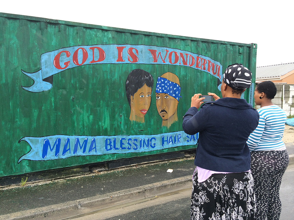 Yolanda Nkatula and Aviwe Dalingozi photograph the mural on a shipping container, home to Mama Blessing Hair Salon in Khayelitsha. The Townships have become like cities and are made up of small commercial shopping malls and independently owned businesses. These businesses sell their goods and services in shacks, shipping containers or simply on the sidewalk. With high unemployment rates in Khayelitsha, it is necessary to find economic opportunities. Most of the containers and shacks are painted with colourful murals with many honouring their strong beliefs.