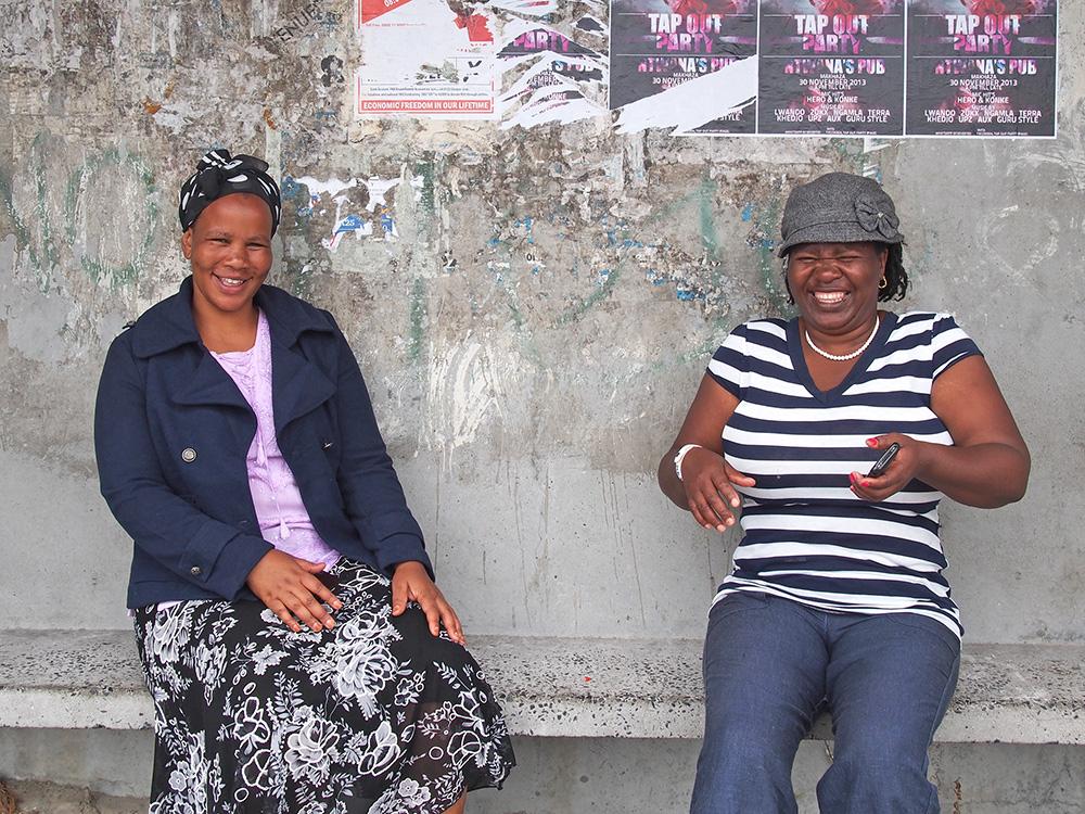 Participants, Yolanda Nkatula and Esther Mahlasela share a laugh at a bus stop in Khayelitsha.