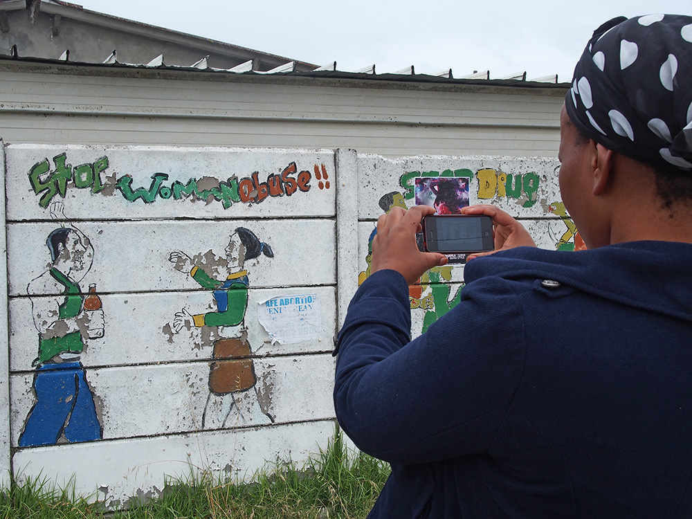 Yolanda Nkatula, a married mother of 2 pauses to photograph a 'Stop Woman Abuse' mural on Walter Sisulu Road in Khayelitsha in November 2013. Many of the fences are painted with street art and showcase anything from advertising a local business to addressing social issues.